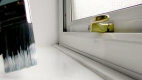 Man att måla en fönsterfönsterbräda med en målarpensel lager videofilmer