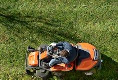 Man att meja en gräsmatta på a ritt-på gräsklippningsmaskinen Arkivfoto