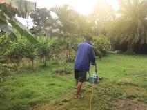 Man att meja gräsmattan i trädgården av hans hus arkivfoto