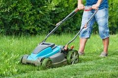 Man att meja gräsmattan med den blåa gräsklipparen i sommartid Arkivfoton
