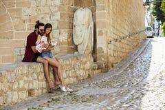 Man att omfamna hans flickvän på en vägg som läser en resehandbok fotografering för bildbyråer