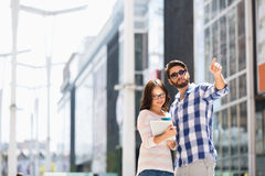 Man att peka medan kvinnan som använder den digitala minnestavlan utanför byggnad Arkivbild