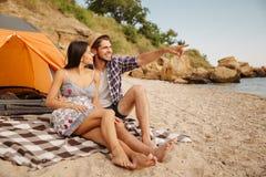 Man att peka på något, medan sitta med flickvännen på stranden Royaltyfria Bilder