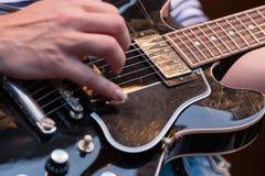 Man att plocka raderna på en elektrisk gitarr Arkivfoto