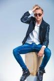 Man att posera bärande solglasögon och att fixa hans hår, medan sitta Arkivfoto