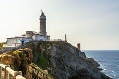 Man att posera för ett foto bredvid fyren i Santander, Spanien fotografering för bildbyråer
