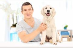 Man att posera med hans hund som inomhus placeras på tabellen Arkivbilder