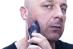 Man att raka av hans skägg med en elektrisk rakapparat Royaltyfri Foto