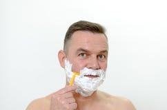 Man att raka hans skägg med en rakkniv och löddra Arkivfoton