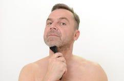 Man att raka hans skägg med en rakkniv och löddra Royaltyfri Bild
