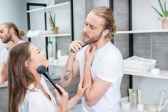 Man att raka hans skägg medan kvinnan som applicerar framsidapulver i badrum arkivbild