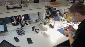 Man att reparera en bruten telefon i avdelningen av garantien arkivfilmer