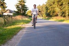 Man att rida en cykel på bygdvägen Royaltyfri Fotografi