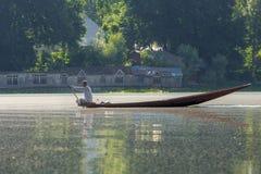 Man att rida ett shikarafartyg på Dal sjön i Srinagar, Kashmir, Indien Fotografering för Bildbyråer