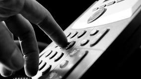 Man att ringa ut på en landlinje telefon Arkivfoto