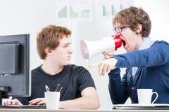 Man att ropa med en megafon till hans kollega Arkivfoto