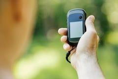 Man att rymma en GPS mottagare och planera i hans hand Royaltyfri Fotografi