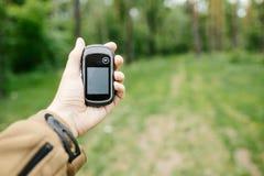 Man att rymma en GPS mottagare och planera i hans hand Arkivbild