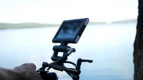 Man att rymma en kamera som filmar en film i den dyra kameran för skogen för film i träna Royaltyfri Fotografi