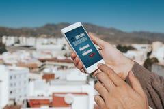 Man att rymma en mobiltelefon i handen med på linjen mobil packa ihop app i skärmen Royaltyfria Foton