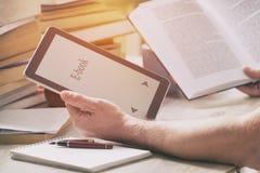 Man att rymma en modern ebookavläsare och bok i arkiv Arkivbild