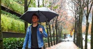 Man att rymma ett paraply och att gå på gatan stock video