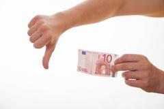 Man att rymma euro tio, och visa tummen underteckna ner royaltyfri foto