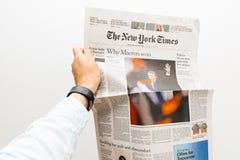Man att rymma på den New York Times tidningen med Emmanuel Macron Arkivbild