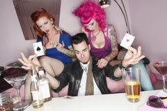 Man att rymma två spela kort med erotiska kvinnlig som sitter förutom honom Fotografering för Bildbyråer
