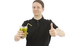 Man att rymma upp ett exponeringsglas av den gröna smoothien och att ge tummar Arkivfoton