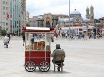 Man att sälja den turkiska bageln Simit och kalla vatten på den Simit vagnen på den Taksim fyrkanten Royaltyfri Bild