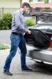Man att sätta bagage in i bilstammen Arkivbild