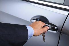 Man att sätta biltangent in i dörrlåset arkivbild