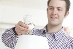 Man att sätta lightbulben för låg energi in i lampan hemma Arkivbilder