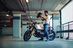 Man att sätta på motorcykelhjälm i ett garage fotografering för bildbyråer