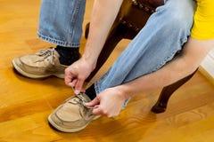 Man att sätta på skor, medan sitta på fotapallen Royaltyfria Bilder