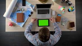Man att söka efter hotellrum i mobil applikation på minnestavlan med den gröna skärmen arkivfoton