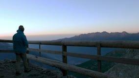 Man att se bergsikt på soluppgång från träbalkong, och dricka den varma drycken från råna, högt upp på fjällängarna arkivfilmer