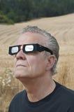 Man att se den sol- förmörkelsen med förmörkelseexponeringsglas Arkivfoton