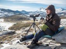 Man att se i bergen med kikare och teleskopet Royaltyfria Bilder