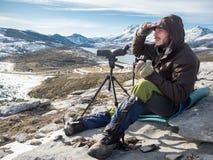 Man att se i bergen med kikare och teleskopet Arkivfoton