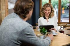 Man att se kvinnan som använder den digitala minnestavlan på coffee shop Fotografering för Bildbyråer