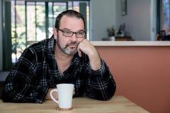Man att se ledset/deprimerat dricka hans morgonkaffe royaltyfri fotografi