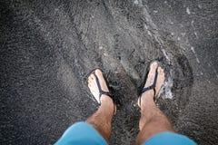 Man att se ner på fot och sandaler på vulkanisk svart sandbeac Royaltyfri Bild