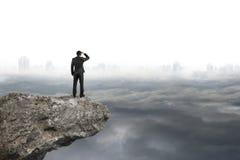 Man att se på klippan med grå cityscapebakgrund för molnig himmel Arkivbild