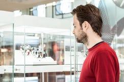 Man att se shoppar fönstret eller monter i köpcentrum Arkivbild