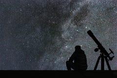 Man att se stjärnorna, astronomiteleskop Stjärnklar Vintergatan fotografering för bildbyråer