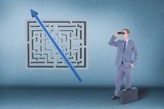 Man att se till och med kikare mot blå bakgrund med en labyrint royaltyfria foton