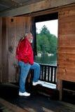 Man att se ut dörröppningen av Watsons Mill täckt br Royaltyfri Fotografi