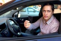 Man att se ut från bilfönster och innehav en billarmtangent Arkivbild